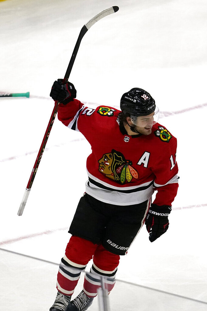 Chicago Blackhawks left wing Alex DeBrincat celebrates after scoring a goal during the first period of an NHL hockey game against the Dallas Stars in Chicago, Sunday, May 9, 2021. (AP Photo/Nam Y. Huh)