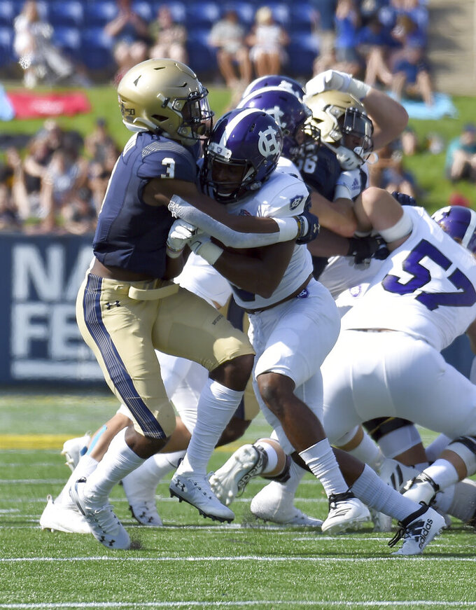 Navy's Cameron Kinley stops Holy Cross' Miles Alexander for a loss on a first quarter run during an NCAA college football game, Saturday, Aug. 31, 2019, in Annapolis, Md. (Paul W. Gillespie/Capital Gazette via AP)