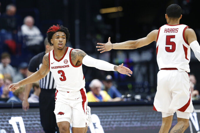 Arkansas guard Desi Sills (3) is congratulated by Jalen Harris (5) after Sills scored against Vanderbilt in the first half of an NCAA college basketball game in the Southeastern Conference Tournament Wednesday, March 11, 2020, in Nashville, Tenn. (AP Photo/Mark Humphrey)