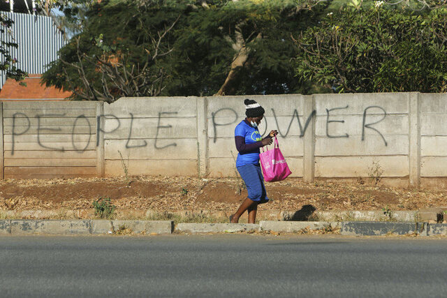A woman walks past a wall with graffiti in Harare, Wednesday, June 10, 2020. Authorities in Zimbabwe have started publicly naming people who have escaped from quarantine centers and urging the public to report them to prevent the spread of the coronavirus. Zimbabwe has seen a rise in confirmed cases of COVID-19 in recent days, with most recorded at quarantine centers. (AP Photo/Tsvangirayi Mukwazhi)