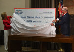 First lady Donna Edwards, left, and Gov. John Bel Edwards, right, unveil a giant check during a news conference at the Louisiana State Capitol in Baton Rouge, La., on Thursday, June 17, 2021, to announce that Louisiana will participate in a lottery, giving cash prizes and scholarships to residents who have been vaccinated against the coronavirus. (Hilary Scheinuk/The Advocate via AP)