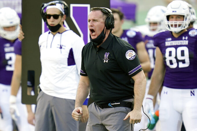 Northwestern head coach Pat Fitzgerald encourages his players on the field during the second half of the Citrus Bowl NCAA college football game against Auburn, Friday, Jan. 1, 2021, in Orlando, Fla. Northwestern beat Auburn 35-19. (AP Photo/John Raoux)