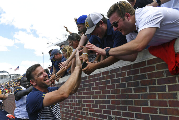 FILE - In this Sept. 21, 2019, file photo, California head coach Justin Wilcox celebrates with fans after an NCAA college football game against Mississippi, in Oxford, Miss. California used a goal-line stand as time ran out to beat Mississippi 28-20, for the Bears' first road win over an SEC school since 1977 and the Pac-12's first since 2010. (AP Photo/Thomas Graning, File)