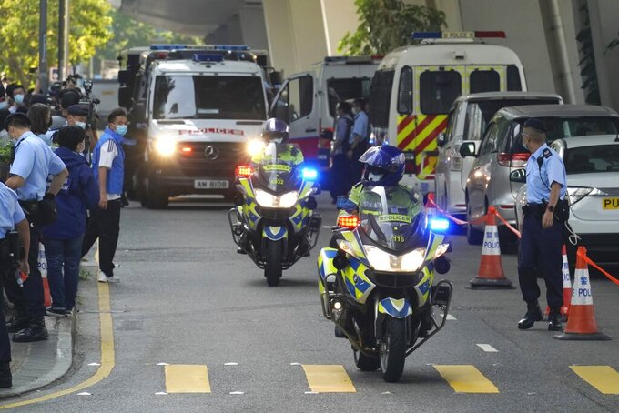 Police officers escort a prison van carrying Hong Kong pro-democracy activist Andy Li as it's leaving court in Hong Kong, Wednesday, April 7, 2021. Li is one of the 12 young pro-democracy activists captured at sea last year by mainland Chinese authorities and returned to Hong Kong in March, as Li is charged with an offense under the newly-invented National Security Law. (AP Photo/Kin Cheung)