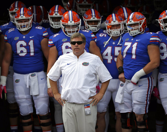 FILE - In this Oct. 28, 2017 file photo then-Florida head coach Jim McElwain, center, prepares to take the field with players before the first half of an NCAA college football game in Jacksonville, Fla. Central Michigan's Jim McElwain is one of four coaches entering their first seasons in the Mid-American Conference. (AP Photo/John Raoux)