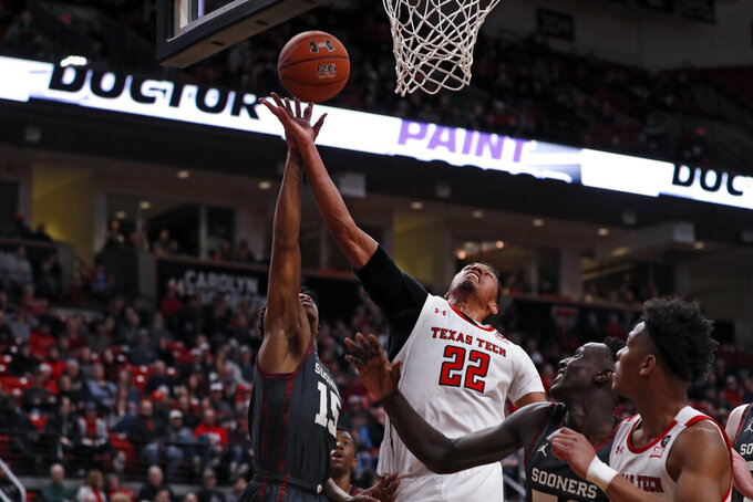 Texas Tech's TJ Holyfield (22) rebounds the ball away from Oklahoma's Alondes Williams (15) during the first half of an NCAA college basketball game Tuesday, Feb. 4, 2020, in Lubbock, Texas. (Brad Tollefson/Lubbock Avalanche-Journal via AP)