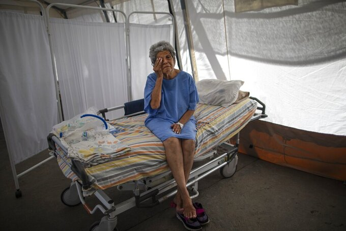 Nancy Rodriguez, a 76-year-old COVID-19 patient, wipes tears as she explains her battle with the virus under a tent for patients who will be discharged from the Peréz de León II Hospital, a public hospital where Doctors Without Borders operates in the Petare neighborhood of Caracas, Venezuela, Monday, Sept. 22, 2020. Venezuela's count of roughly 800 COVID-19 deaths among its more than 90,000 cases is likely an undercount, as many are fearful of the broken health care system and choose to stay home. (AP Photo/Ariana Cubillos)