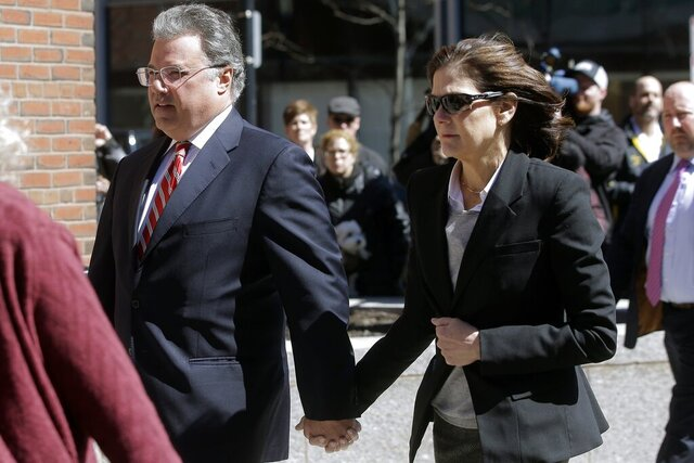 FILE - In this April 3, 2019, file photo, Manuel and Elizabeth Henriquez arrive at federal court in Boston to face charges in a nationwide college admissions bribery scandal. Henriquez and her husband were charged with paying $400,000 in bribes to get their oldest daughter into Georgetown as a bogus tennis recruit in 2016. They also paid bribes to have someone cheat on their daughters' college entrance exams, authorities said. (AP Photo/Steven Senne, File)