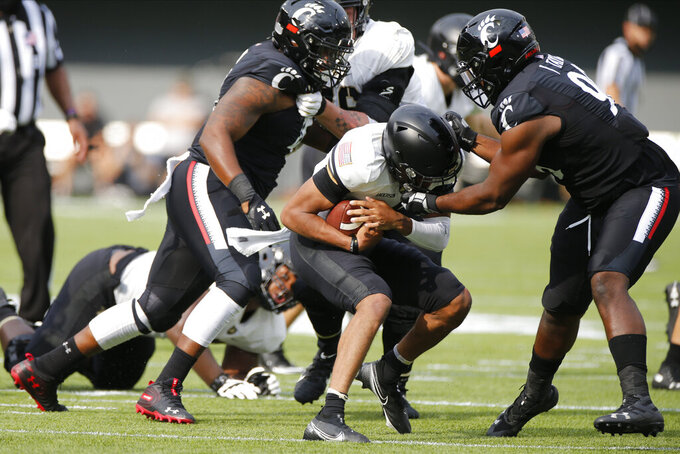 Cincinnati defensive lineman Jabari Taylor, right, sacks Army quarterback Christian Anderson during the first half of an NCAA college football game Saturday, Sept. 26, 2020, in Cincinnati, Ohio. (AP Photo/Jay LaPrete)