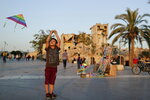 In this Saturday, July 27, 2019 photo, a  child flies a kite in front of the ancient Citadel as Syrian in Aleppo, Syria. Rebels still frequently strike with shelling and mortars into Aleppo, killing civilians nearly three years after the government recaptured the city. Aleppo is a symbol of how President Bashar Assad succeeded in turning the tide in Syria's long civil war with a series of wins, but it's equally a symbol of how he's been unable to secure a final victory. Half of Aleppo remains in ruins, and rebels remain on the doorstep. (AP Photo/Hassan Ammar)