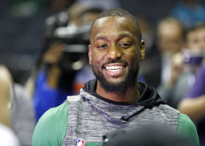 Boston Celtics' Kemba Walker smiles with friends as he makes his way onto the Charlotte Hornets' court before an NBA basketball game between the Celtics and the Hornets in Charlotte, N.C., Thursday, Nov. 7, 2019. Walker formerly played for the Hornets. (AP Photo/Bob Leverone)