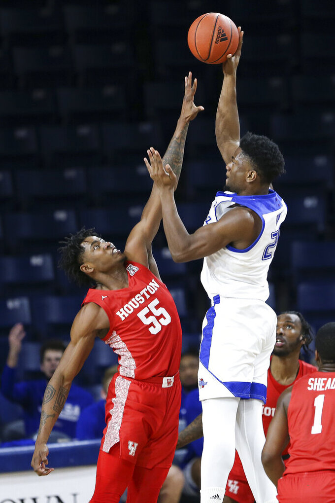 Tulsa's Emmanuel Ugboh goes up for a shot against Houston's Brison Gresham during the second half of an NCAA college basketball game in Tulsa, Okla., Tuesday, Dec. 29, 2020. Tulsa won 65-64. (AP Photo/Dave Crenshaw)