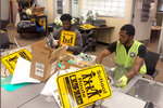 In this Jan. 16, 2020 photo, Nicholas Thomas, left, and Joe Wright, right, prepare school safety signs as part of the AmeriCorps Urban Safety Program at Wayne State University's Center for Urban Studies. Volunteers will post the signs and also help board up vacant houses Monday near a Detroit school as part of an annual project commemorating the Rev. Martin Luther King Jr's birthday and the federal holiday. (AP Photo/Corey Williams)