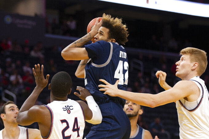 Nevada forward K.J. Hymes (42) pulls down a rebound over Saint Mary's forwards Malik Fitts (24) and Matthias Tass (11) during the first half of an NCAA college basketball game Saturday, Dec. 21, 2019, in San Francisco. (AP Photo/D. Ross Cameron)