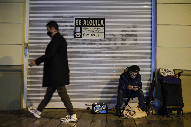 A homeless with his little pet, bottom right, in front a store to rent for food, begs for alms while pedestrian walking past wearing face mask protection against the coronavirus, in Pamplona, northern Spain, Thursday, Jan. 21, 2021. (AP Photo/Alvaro Barrientos)
