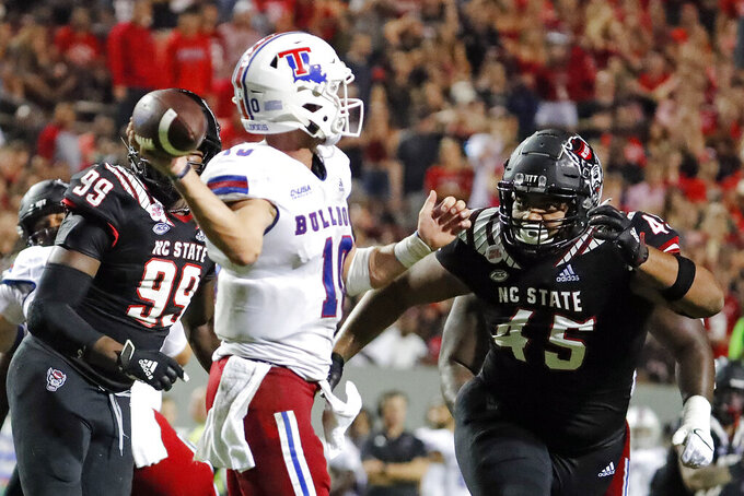 Louisiana Tech's Austin Kendall (10) is rushed to throw the ball by North Carolina State's Davin Vann (45) during the first half of an NCAA college football game in Raleigh, N.C., Saturday, Oct. 2, 2021. (AP Photo/Karl B DeBlaker)