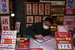 In this Feb. 13, 2020, photo, a vendor wears a mask while writing calligraphy for customers in Yokohama's Chinatown, near Tokyo. A top Olympic official made clear Friday the 2020 Games in Tokyo will not be cancelled despite the virus that has spread from China. (AP Photo/Jae C. Hong)