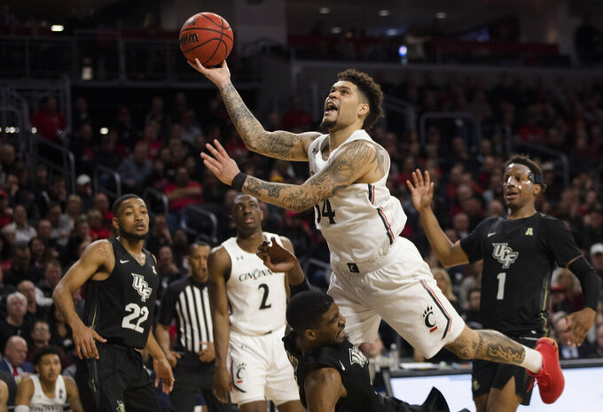 Cincinnati guard Jarron Cumberland (34) shoots as Central Florida forward Collin Smith (35) is charged with a blocking foul during the second half of an NCAA college basketball game Wednesday, Feb. 19, 2020, in Cincinnati. (Albert Cesare/The Cincinnati Enquirer via AP)