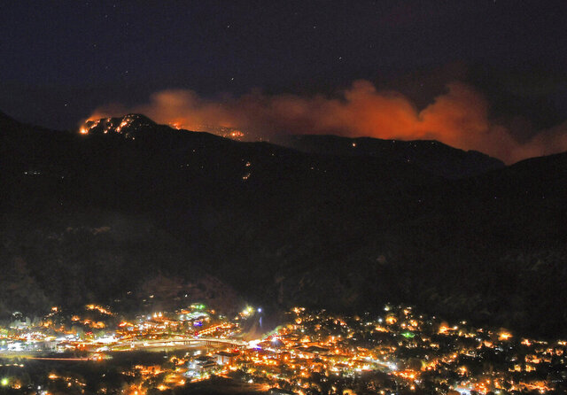 Embers from the Grizzly Creek Fire illuminate the mountains above Glenwood Springs, Colo., on the evening of Thursday, Aug. 13, 2020. Wildfires burning in western Colorado continue to grow in warm, windy weather, fueled by drought conditions. The Grizzly Creek Fire initially broke out along interstate 70 in Glenwood Canyon just east of Glenwood Springs. (Chelsea Self/Glenwood Springs Post Independent via AP)