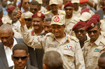 Gen. Mohammed Hamdan Dagalo, the deputy head of the military council, better known as Hemedti, center, escorted by his bodyguards, as he waves to his supporters during a military-backed rally, in Mayo district, south of Khartoum, Sudan, Saturday, June 29, 2019. Sudan's ruling generals say they have accepted a joint proposal from the African Union and Ethiopia to work toward a transitional government. (AP Photo/Hussein Malla)