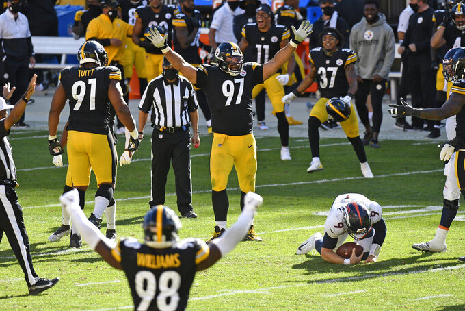 Pittsburgh Steelers defensive tackle Cameron Heyward (97) celebrates a sack of Denver Broncos quarterback Jeff Driskel (9) by Steelers strong safety Terrell Edmunds (34) late in the second half of an NFL football game in Pittsburgh, Sunday, Sept. 20, 2020. (AP Photo/Don Wright)