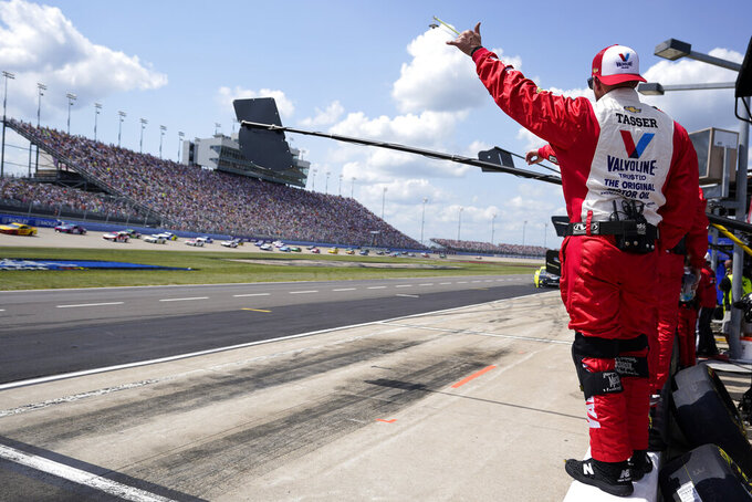 Pit crew members for driver Aric Almirola wave as cars circle the track before the start of a NASCAR Cup Series auto race at Nashville Superspeedway Sunday, June 20, 2021, in Lebanon, Tenn. (AP Photo/Mark Humphrey)
