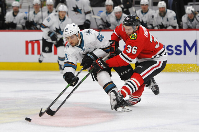 Chicago Blackhawks' Matthew Highmore (36) battles San Jose Sharks' Kevin Labanc (62) for a loose puck during the third period of an NHL hockey game Wednesday, March 11, 2020, in Chicago. Chicago won 6-2. (AP Photo/Paul Beaty)