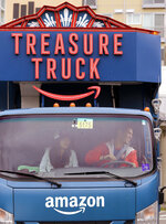 In this May 24, 2018, photo Amazon worker Tony Biallas, right, backs-up an Amazon Treasure Truck into a parking spot as intern Mavis Rong rides shotgun in Seattle. The Treasure Truck is a quirky way for the online retailer to connect with shoppers in person, expand its physical presence and promote itself. Amazon has also used the trucks to try to bring people into Whole Foods, the grocery chain it bought last year. The trucks debuted two years ago and now roam nearly dozens of cities in the United States and England. (AP Photo/Elaine Thompson)