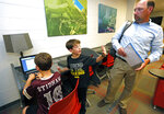 In this May 8, 2019, photograph, Graham Stidham, center, asks his father, East Webster High School Assistant Principal Corey Stidham, for a few more minutes of internet use so his brother, Miles, left, can finish his educational game, at the school's laptop bank in Maben, Miss. The Stidhams are unable to get internet at their rural home, so they take advantage of the internet in the school's library to do homework. (AP Photo/Rogelio V. Solis)