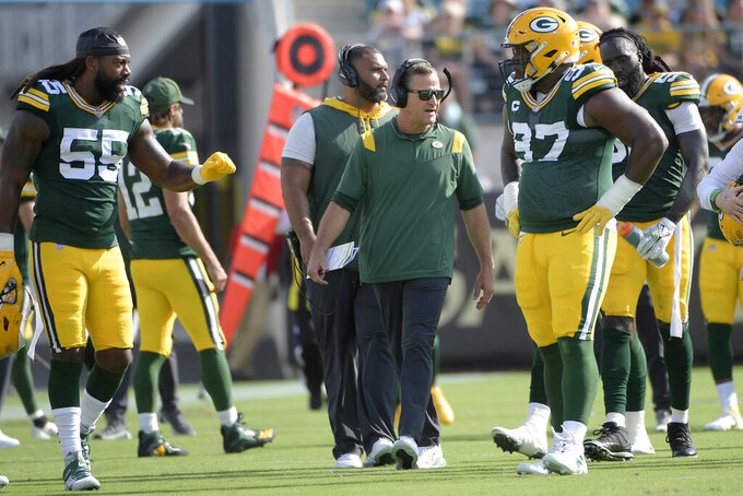 FILE - In this Sunday, Sept. 12, 2021, file photo, Green Bay Packers defensive coordinator Joe Barry, center, works with outside linebacker Za'Darius Smith (55) and nose tackle Kenny Clark (97) during a break in the first half of an NFL football game against the New Orleans Saints, in Jacksonville, Fla. Barry said at his introductory news conference that the adversity he encountered in two unsuccessful stints filling the same role in Detroit and Washington made him a better coach. (AP Photo/Phelan M. Ebenhack, File)