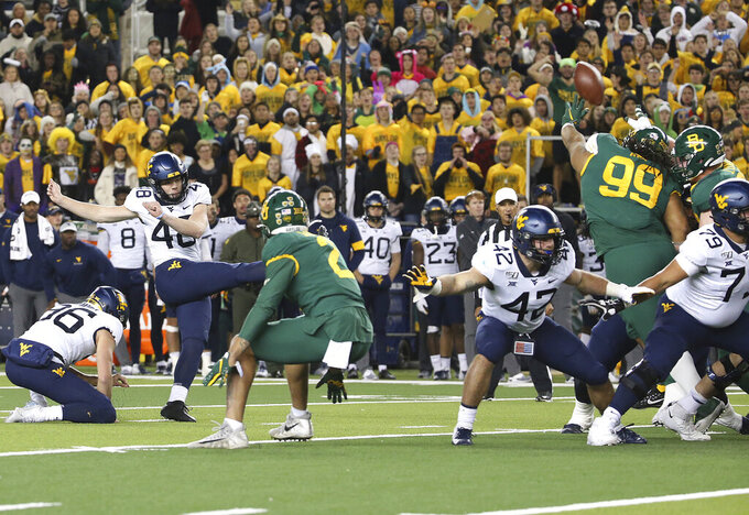 Baylor defensive tackle Bravvion Roy (99), blocks a field goal attempt by West Virginia's Casey Legg (48) during the second half of an NCAA college football game in Waco, Texas, Thursday, Oct. 31, 2019. Baylor won 17-14. (AP Photo/Jerry Larson)