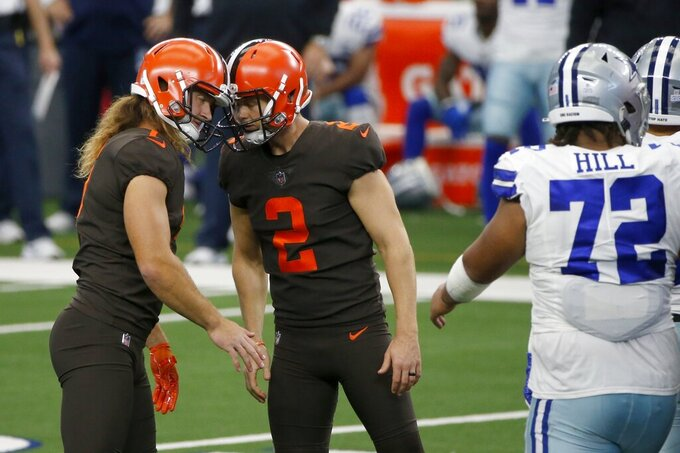 Cleveland Browns' Jamie Gillan, left, and Cody Parkey (2) celebrate a field goal kicked by Parkey as Dallas Cowboys' Trysten Hill (72) looks on in the second half of an NFL football game in Arlington, Texas, Sunday, Oct. 4, 2020. (AP Photo/Michael Ainsworth)