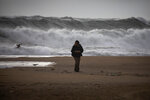 A man walks at the beach during strong winds in Barcelona, Spain, Monday, Jan. 20, 2020. Two people have died as storms carrying heavy snowfalls and gale-force winds lashed many parts of Spain on Monday. The storm has forced the closure of Alicante airport and some 30 roads in eastern region. Six provinces are on top alert. (AP Photo/Emilio Morenatti)