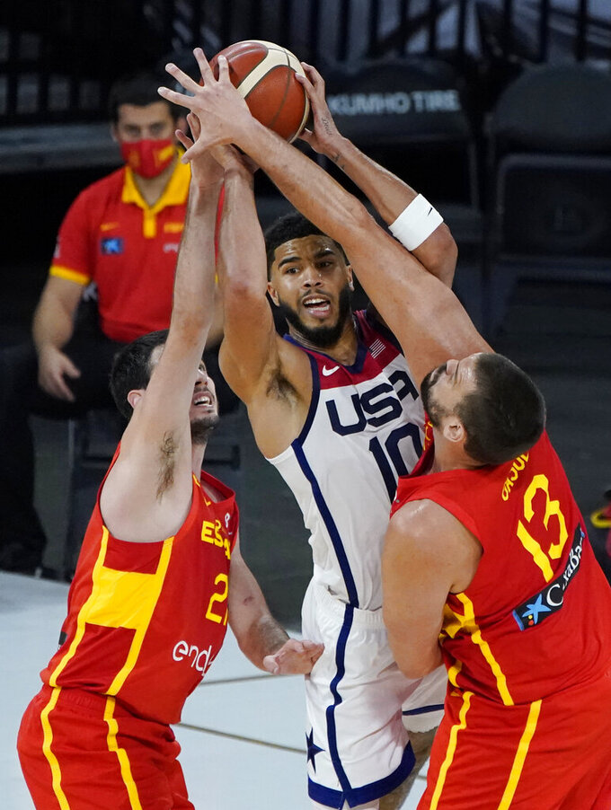 United States' Jayson Tatum (10) passes around Spain's Alex Abrines, left, and Spain's Marc Gasol (13) during the second half of an exhibition basketball game in preparation for the Olympics, Sunday, July 18, 2021, in Las Vegas. (AP Photo/John Locher)