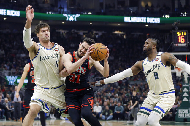 Chicago Bulls' Tomas Satoransky (31) drives to the basket between Milwaukee Bucks' Brook Lopez (11) and Wesley Matthews (9) during the first half of an NBA basketball game Monday, Jan. 20, 2020, in Milwaukee. (AP Photo/Aaron Gash)