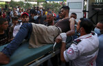 Medics move a wounded youth, who was shot by Israeli troops in his leg during a protest at the Gaza Strip's border with Israel, into the treatment room of Shifa hospital in Gaza City, Saturday, Aug. 21, 2021. (AP Photo/Abdel Kareem Hana)