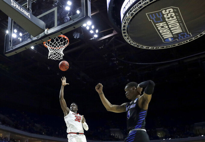 Texas Tech's Norense Odiase (32) gets past Buffalo's Davonta Jordan (4) to put up a shot during the second half of a second round men's college basketball game in the NCAA Tournament Sunday, March 24, 2019, in Tulsa, Okla. Texas Tech won 78-58. (AP Photo/Charlie Riedel)