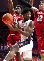 Illinois guard Andres Feliz (10) passes away from the defense of Wisconsin guard Khalil Iverson (21) and forward Ethan Happ (22) during the first half of an NCAA college basketball game in Champaign, Ill., Wednesday, Jan. 23, 2019. (AP Photo/Stephen Haas)