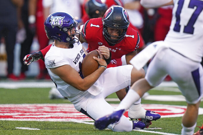 Weber State quarterback Bronson Barron, left, slides as Utah linebacker Nephi Sewell (1) closes in for the tackle during the first half of an NCAA college football game Thursday, Sept. 2, 2021, in Salt Lake City. (AP Photo/Rick Bowmer)