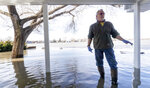 Tim Bazar stands on the back deck of his flooded house Friday, March 22, 2019, in Bellevue, Neb. Flooding in Nebraska has caused an estimated $1.4 billion in damage. The state received Trump's federal disaster assistance approval on Thursday. (Kent Sievers-/Omaha World-Herald via AP)