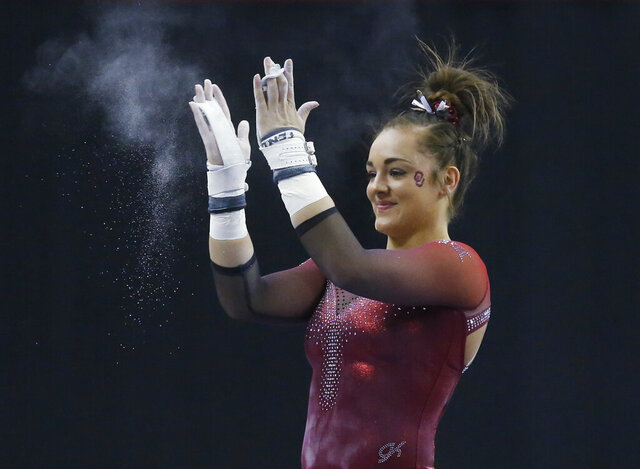 FILE - In this Feb. 16, 2019, file photo, Oklahoma gymnast Maggie Nichols reacts after her routine on the uneven bars in the Perfect 10 Challenge at the Bart and Nadia Sports Experience in Oklahoma City. Nichols' gymnastics career came to an abrupt end last month due to the COVID-19 pandemic. The world championship gold medalist and NCAA champion's legacy however, extends far beyond the floor. Nichols played a key role in exposing the abusive behavior of disgraced doctor Larry Nassar.(AP Photo/Sue Ogrocki, File)