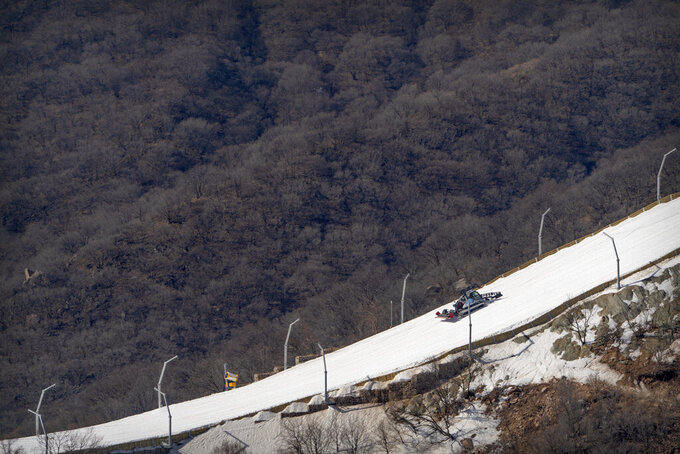 A machine grooms a ski run lined with artificial snow at the National Alpine Skiing Center in Yanqing on the outskirts of Beijing, Friday, Feb. 5, 2021. Beijing Olympic organizers showed off the downhill skiing venue and the world's longest bobsled and luge track Friday, one year ahead of the scheduled opening of the 2022 Olympic Winter Games. (AP Photo/Mark Schiefelbein)