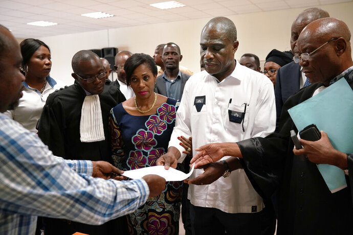 Accompanied by his wife and his lawyers, Congo opposition candidate Martin Fayulu receives the receipt after petitioning the constitutional court following his loss in the presidential elections in Kinshasa, Congo, Saturday Jan. 12, 2019. The ruling coalition of Congo's outgoing President Joseph Kabila has won a large majority of national assembly seats, the electoral commission announced Saturday, while the presidential election runner-up was poised to file a court challenge alleging fraud. (AP Photo/Jerome Delay)