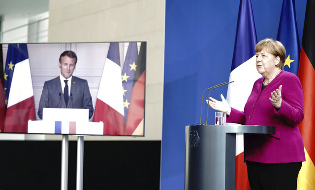 German Chancellor Angela Merkel talks to French President Emmanuel Macron, connected by video, during a press conference after a joint video conference in Berlin, Germany, Monday, May 18, 2020. One topic was the corona pandemic and its consequences. (Kay Nietfeld/dpa via AP)