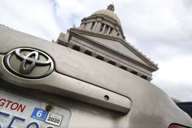 A car registration tab is shown on a vehicle parked at the Capitol, Wednesday, Feb. 12, 2020, in Olympia, Wash. A King County Superior Court judge on Wednesday rejected most of a legal challenge to Tim Eyman's Initiative 976, a measure that would steeply discount the price of car registrations while gutting transportation budgets across the state. (AP Photo/Ted S. Warren)