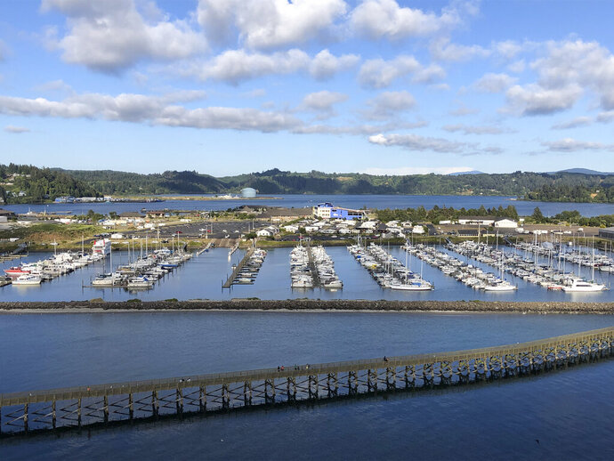 FILE - In this July 22, 2019, file photo, Oregon State University's Marine Studies Building, which is under construction in a tsunami inundation zone, is viewed from the Yaquina Bay Bridge in Newport, Ore. The building, center right, is surrounded by Yaquina Bay. The Oregon Legislature appears poised to continue to allow construction of critical facilities in tsunami inundation zones, a move slammed by critics. (AP Photo/Andrew Selsky, File)