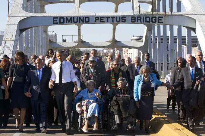 """FILE - In this March 7, 2015, file photo, singing """"We Shall Overcome,"""" President Barack Obama, third from left, walks holding hands with Amelia Boynton, who was beaten during """"Bloody Sunday,"""" as they and the first family and others including Rep. John Lewis, D-Ga, left of Obama, walk across the Edmund Pettus Bridge in Selma, Ala., for the 50th anniversary of """"Bloody Sunday,"""" a landmark event of the civil rights movement. (AP Photo/Jacquelyn Martin, File)"""