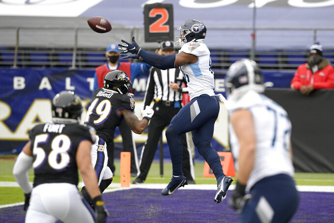 Tennessee Titans tight end Jonnu Smith, center, prepares to catch a touchdown pass from Tennessee Titans quarterback Ryan Tannehill, not visible, during the first half of an NFL football game against the Baltimore Ravens, Sunday, Nov. 22, 2020, in Baltimore. (AP Photo/Nick Wass)