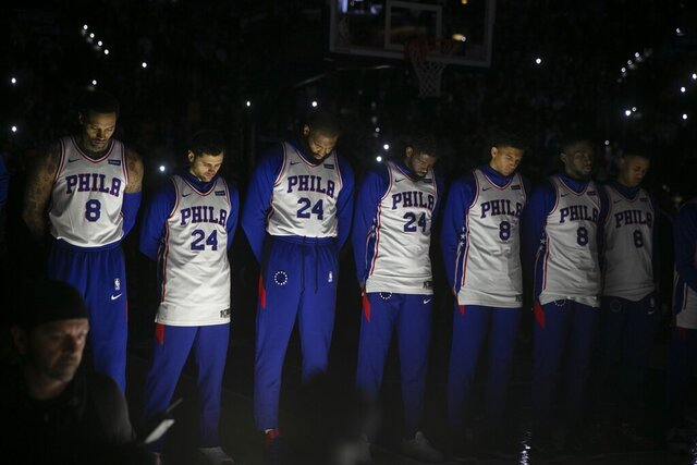 Philadelphia 76ers stand during a tribute to Kobe Bryant, before the team's NBA basketball game against the Golden State Warriors on Tuesday, Jan. 28, 2020, in Philadelphia. Bryant died along with his daughter and seven other people during helicopter crash Sunday. (Steven M. Falk/The Philadelphia Inquirer via AP)