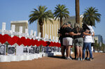FILE - In this Oct. 1, 2019, file photo, people pray at a makeshift memorial for shooting victims in Las Vegas, on the anniversary of the mass shooting two years earlier. The casino company that owns the former Las Vegas Strip concert venue that became the site of the deadliest mass shooting in modern American history said Monday, Aug. 2, 2021, it is donating part of the property for a permanent memorial. (AP Photo/John Locher, File)